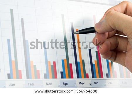Business financial analysis concept with hand holding a pen - stock photo