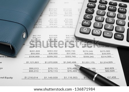 business financial chart analysis with pen, notebook & calculator on paper work - stock photo