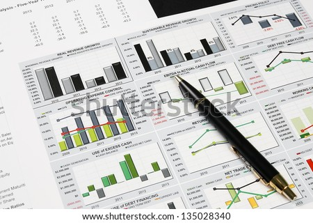 business financial chart analysis with pen on paper work - stock photo