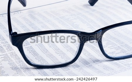 business financial newspaper report see through glasses lens, workplace of the businessman, concept of business