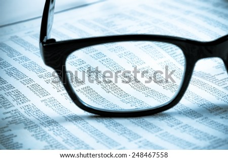 business financial newspaper report see through glasses lens, workplace of the businessman, concept of business - stock photo