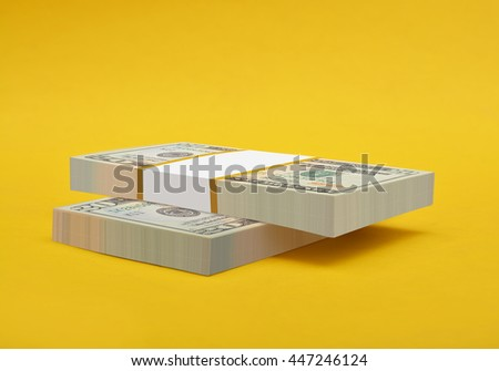 Business, financial success and making money concept, stacks of 20 US dollar banknotes or bills isolated on yellow background  - stock photo