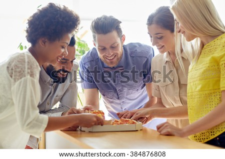 business, food, lunch and people concept - happy business team or friends eating pizza in office - stock photo