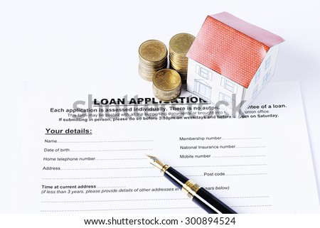 Business fountain pen and coins stack and house paper on loan application