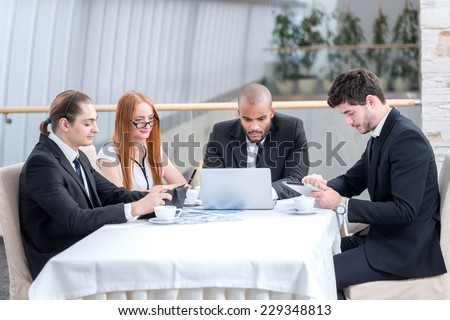 Business friendships. Four smiling successful businessmen at a meeting while sitting at a table discussing business affairs in the office