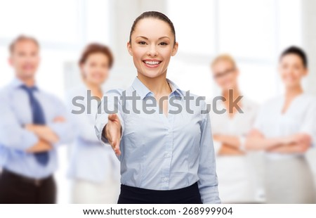 business, gesture and education concept - friendly young smiling businesswoman with opened hand ready for handshake over group of people background - stock photo