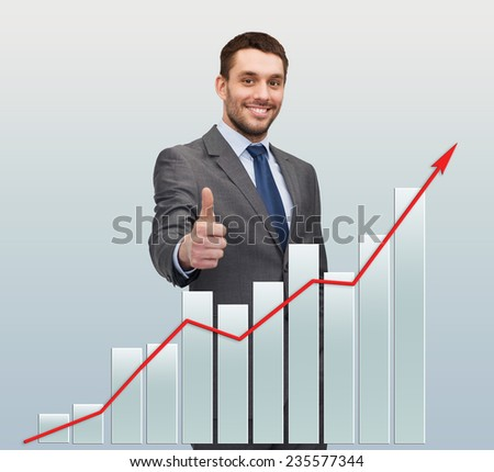 business, gesture and people concept - smiling handsome businessman showing thumbs up over gray background with graph