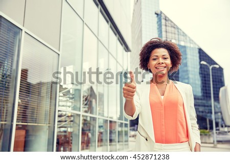 business, gesture and people concept - young smiling african american businesswoman in city showing thumbs u p - stock photo