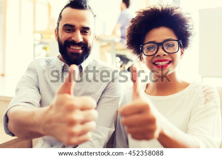 business, gesture, success, startup and people concept - happy international creative team at office showing thumbs up - stock photo