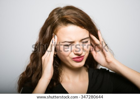 Business girl has a severe headache, studio shot isolated on the gray background