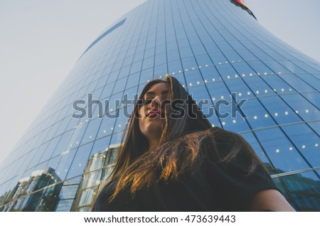 business girl in a black dress closeup on background of modern building