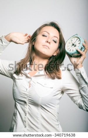 business girl overslept and yawns. alarm clock, office manager. studio photo on a gray background - stock photo