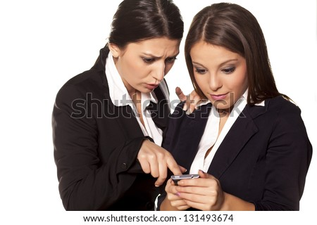 business girl shows to her friend with a finger on her smart phone