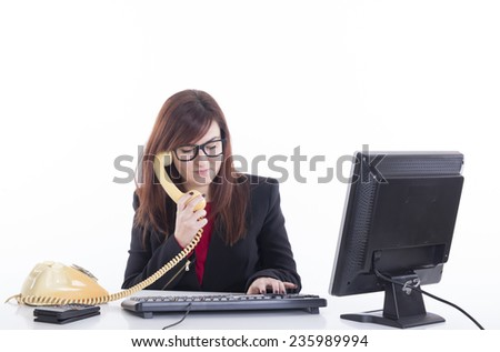 Business girl using telephone and computer at office - stock photo