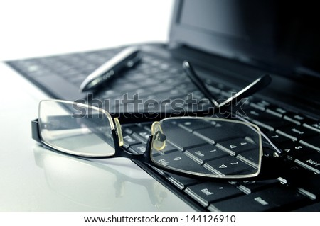 Business - Glasses and ball pen on top of a laptop