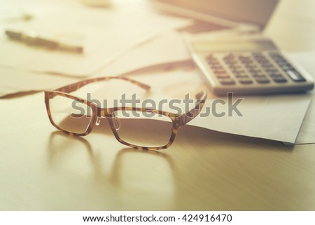 Business,Glasses on Office desk table with computer, supplies and chart graph for analyzing financial chart,writing business plan,side view with copy space,vintage color,selective focus - stock photo