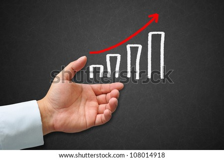 Business graph on a blackboard with hand - stock photo