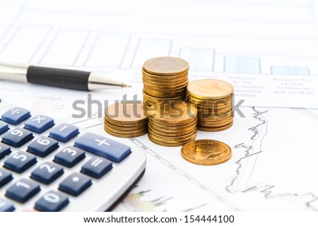 Business graph on paper report with coins - stock photo