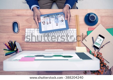 Business graphs against businessman holding digital tablet while sitting at computer desk - stock photo