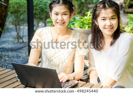 Business green garden two asian women discussing of work on wood table outdoor