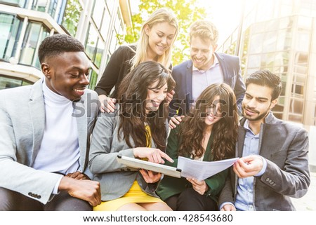 Business group during break looking at digital tablet. They all are young, smiling and wearing smart casual clothes. Mixed race group. Teamwork and business concepts. - stock photo