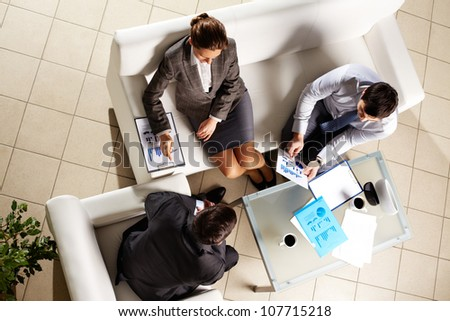 Business group holding a meeting to discuss financial data - stock photo