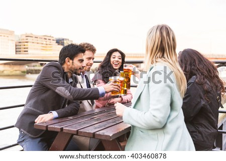 Business group in London drinking beer after work. They all are young, smiling and wearing smart casual clothes. Mixed race group. Also could refer to a group of friends. - stock photo