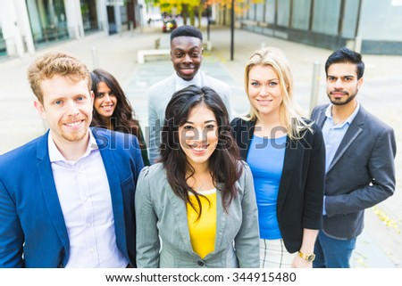 Business group looking at camera. They all are young, smiling and wearing smart casual clothes. Mixed race group, three women and three men. Teamwork and business concepts.