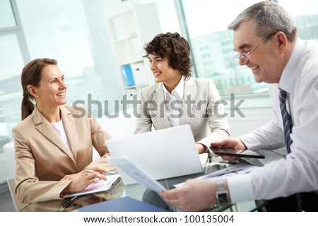 Business group of diverse age discussing some matters, tilt up - stock photo