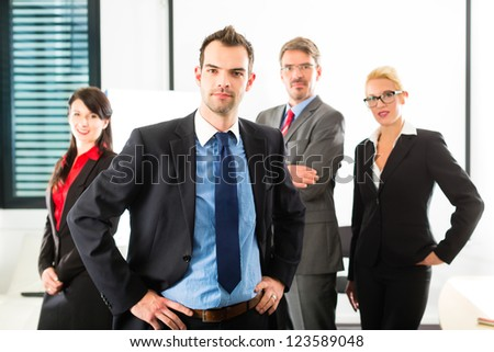 Business - group of successful and confident businesspeople being a team and showing it - stock photo