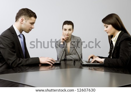 Business group portrait - Young man and two women working together on laptops - stock photo