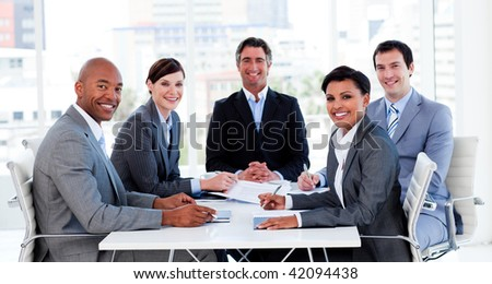 Business group showing ethnic diversity in a meeting smiling at the camera - stock photo
