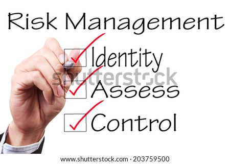 business hand checking the checklist boxes risk management identity assess control by pen on transparent glass  - stock photo