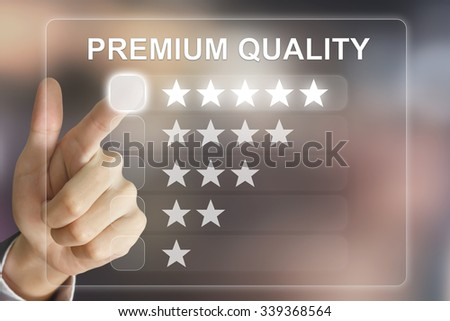 business hand clicking premium quality on virtual screen interface - stock photo