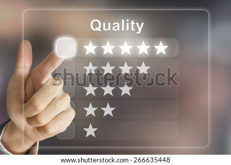 business hand clicking quality on virtual screen interface - stock photo