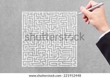 business hand finding solution of maze - stock photo