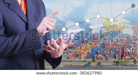 Business hand hold digital tablet with increasing chart of transport business,Industrial Container Cargo freight ship at port is background(Elements of this image furnished by NASA)