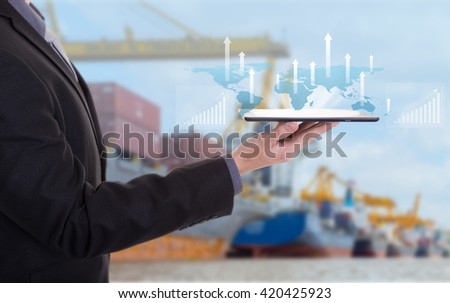 Business hand hold tablet with digital layer effect as business target concept,Industrial Container Cargo freight ship for Logistic Import Export background (Elements of this image furnished by NASA)