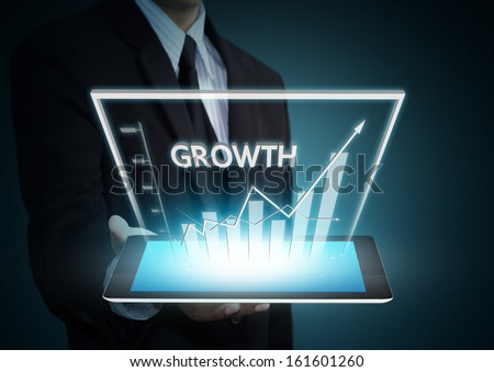 Business hand holding growth graph on tablet technology - stock photo