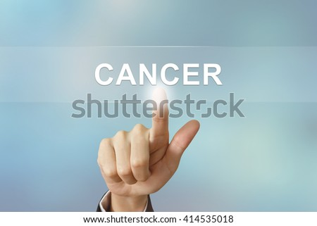 business hand pushing cancer button on blurred background
