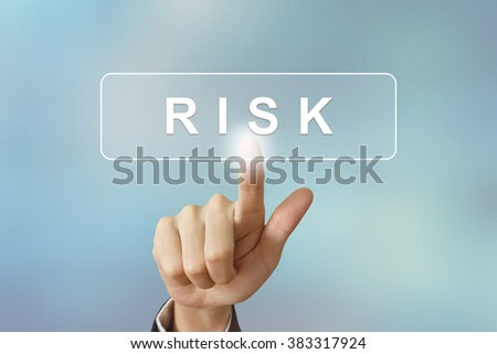 business hand pushing risk button on blurred background