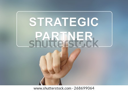 business hand pushing strategic partner button on blurred background - stock photo