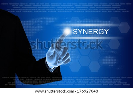 business hand pushing synergy button on a touch screen interface  - stock photo