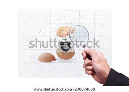 business hand searching success by magnifying glass on jigsaw concept of brain inside a light bulb an egg cracking open against  white background with clipping path - stock photo