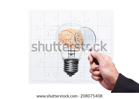 business hand searching success by magnifying glass on jigsaw concept of brain inside a light bulb against  white background with clipping path - stock photo