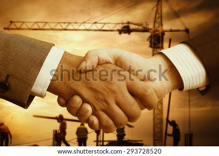 business hand shake and a office in background - stock photo