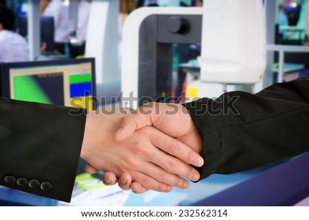 Business hand shake with machinery background - stock photo