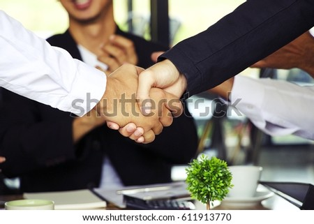 Business hand shakes with blurred man is clapping background