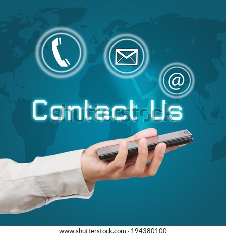 Business hand showing smartphone with  word contact us and icon on virtual screen. - stock photo