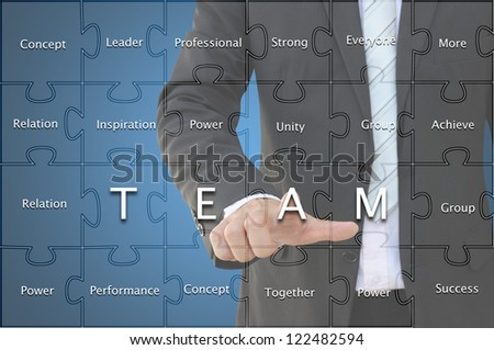 Business hand with team concept in jigsaw pattern - stock photo